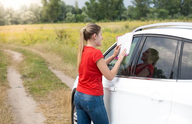 Schöne junge frau hat sich auf dem feld verirrt, während sie ein auto fuhr und eine papierkarte las