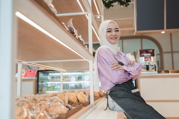 Schöne junge frau hijab, die stolz an ihrem geschäft lächelt. attraktive asiatische junge ladenbesitzerin