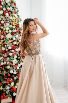 Schöne junge frau im abendkleid nahe weihnachtsbaum. fröhliche weihnachten