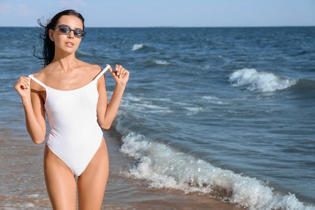 Schöne junge frau im badeanzug am meeresstrand