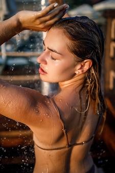 Schöne junge frau im badeanzug mit einer perfekten figur in der dusche im abendlicht am meer. mädchen mit goldener bräune im urlaub