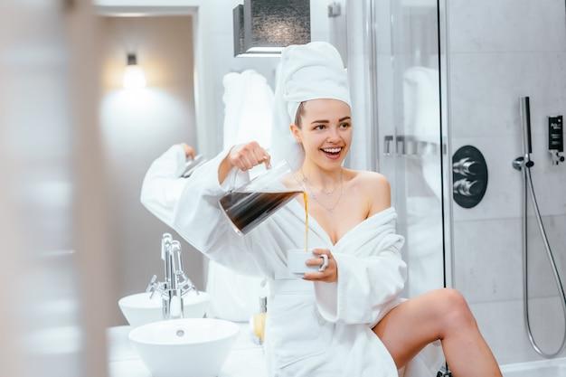 Schöne junge frau im bademantel und im tuch auf ihrem kopf, der auf einer badewanne sitzt