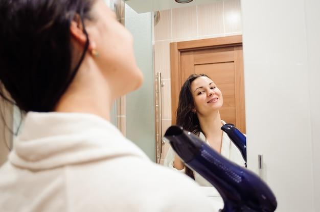 Schöne junge frau im badetuch benutzt einen fön und lächelt, während sie in den spiegel im badezimmer schaut.