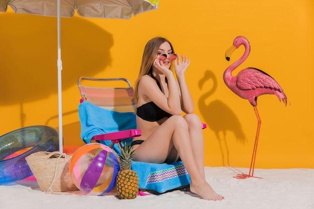 Schöne junge frau im bikini, der auf daybed im studio sitzt