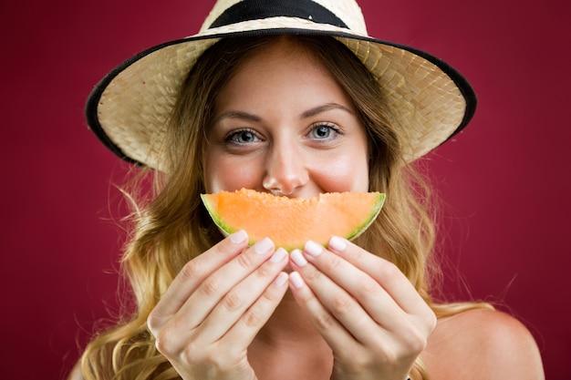 Schöne junge frau im bikini essen melone. isoliert auf rot.