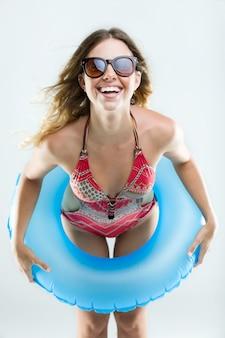 Schöne junge frau im bikini spielen mit schwimmer. isoliert auf weiß.