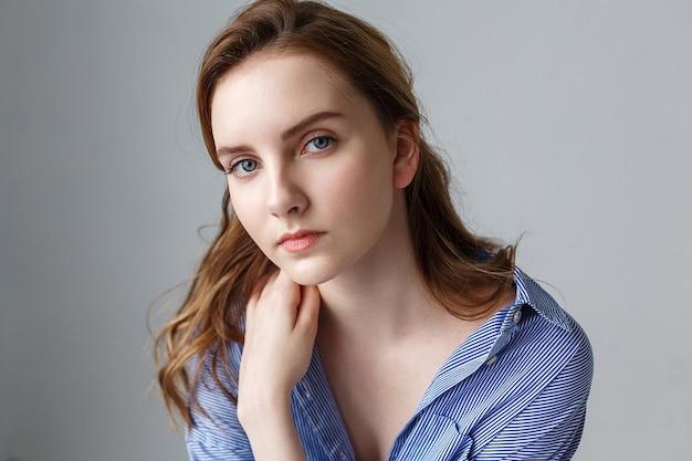 Schöne junge frau im blau gestreiften hemd, das ihren arm auf schulter, porträt des niedlichen modells hält. natürliche hübsche dame, die im studio aufwirft
