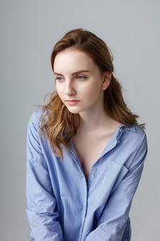 Schöne junge frau im blau gestreiften hemd, innenporträt des niedlichen nachdenklichen modells. natürliche hübsche dame, die im studio aufwirft