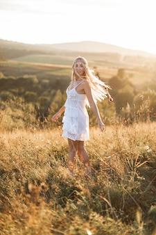 Schöne junge frau im boho-stil im weißen kleid und mit federn im haar, die am sommerfeld gehen