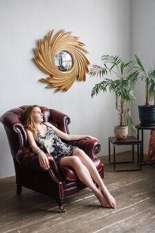 Schöne junge frau im bunten kleid, innenporträt des niedlichen nachdenklichen modells. im sessel in einem gemütlichen raum sitzen. natürliche hübsche dame, die zu hause posiert