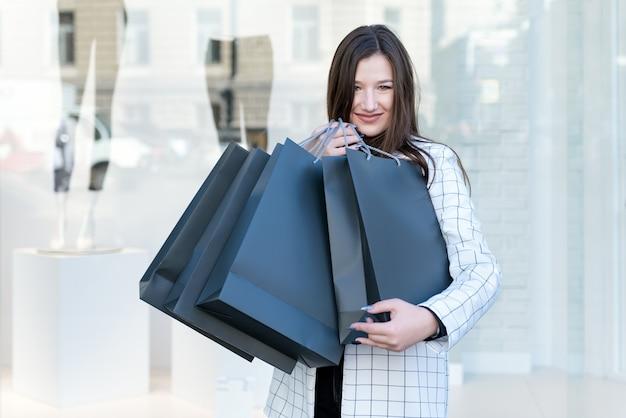 Schöne junge frau im einkaufszentrum mit einkäufen. porträt der käuferin auf schaufensterhintergrund. attrappe, lehrmodell, simulation.