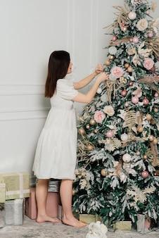 Schöne junge frau im eleganten kleid, das nahe bei weihnachtsbaum und geschenken steht.