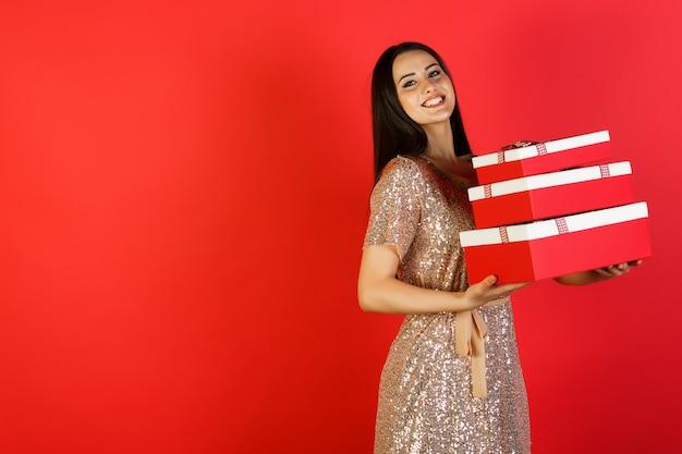 Schöne junge frau im eleganten kleid mit weihnachtsgeschenken auf rotem hintergrund