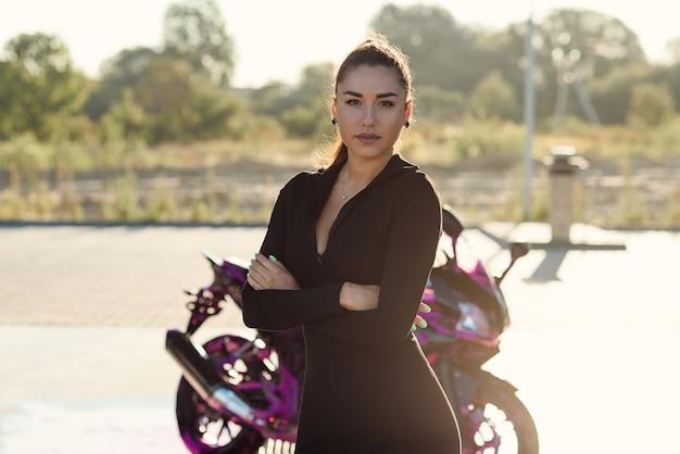 Schöne junge frau im eng anliegenden schwarzen anzug wirft nahe sportmotorrad am selbstbedienungsauto auf