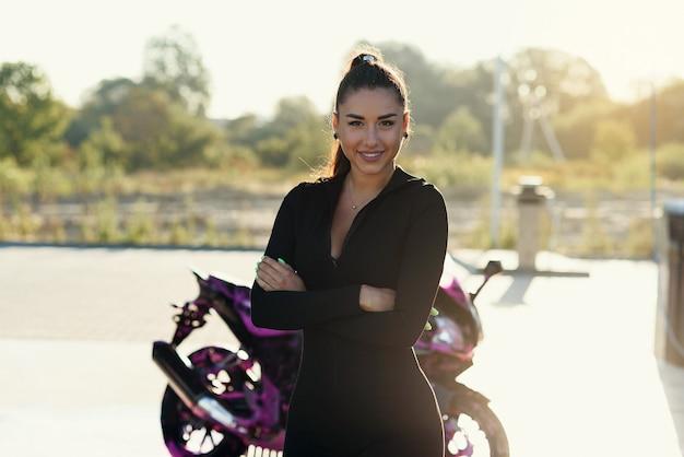 Schöne junge frau im eng anliegenden schwarzen anzug wirft nahe sportmotorrad bei selbstbedienungsautowaschanlage auf