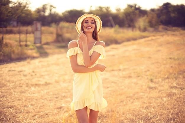 Schöne junge frau im freien auf dem hügel an einem sommertag