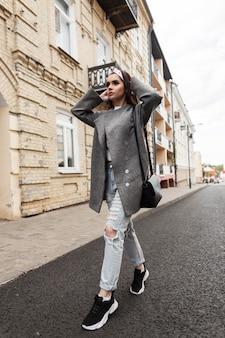 Schöne junge frau im glamour-bandana mit schwarzer tasche im grauen mantel mit handtasche in schuhen geht in der nähe des vintage-gebäudes auf der straße. stilvolles mädchenmodell reisen auf der straße in der stadt