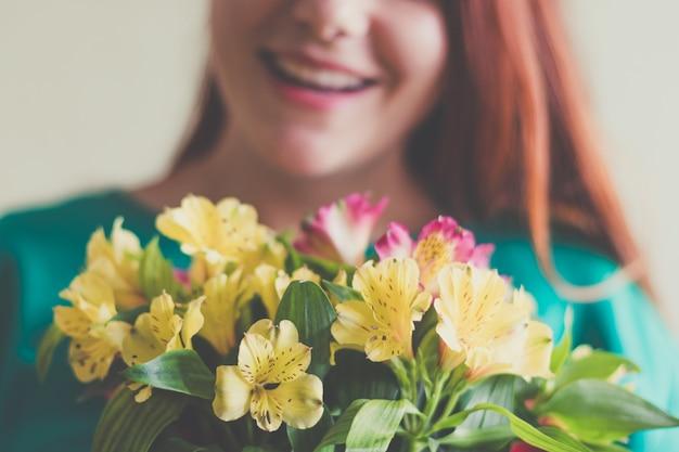 Schöne junge frau im grünen kleid, das frühlingsblumenblumenstrauß hält