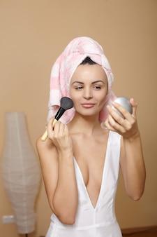 Schöne junge frau im handtuch auf dem kopf, der make-up im spiegel aufträgt