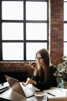 Schöne junge frau im heimbüro. von zu hause aus arbeiten. telearbeitskonzept