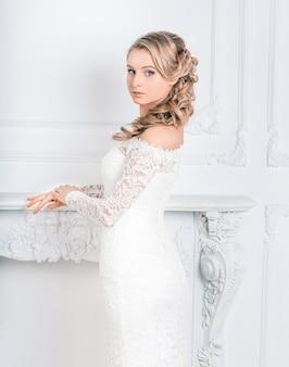 Schöne junge frau im hochzeitskleid, das im hochzeitssalon steht.