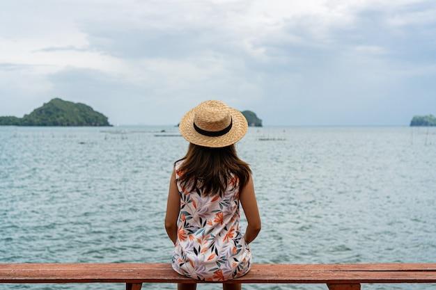 Schöne junge frau im hut sitzt auf roter bank, die den tropischen strand betrachtet.