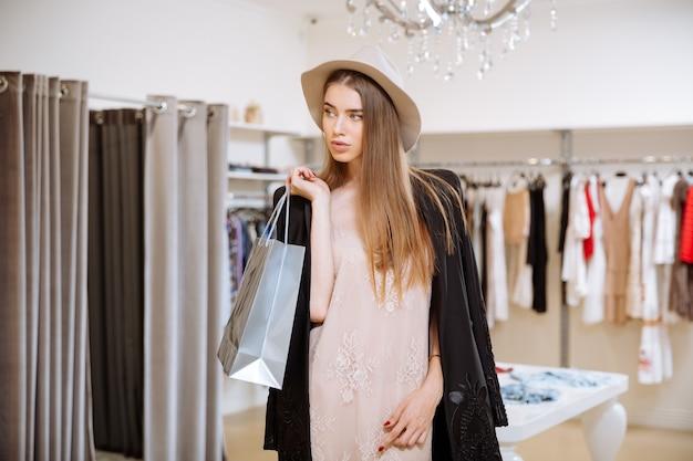 Schöne junge frau im hut stehend und hält einkaufstaschen in der modeboutique