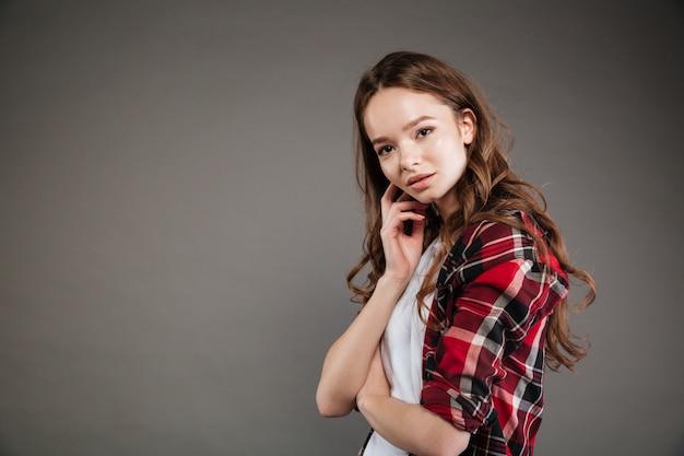Schöne junge frau im karierten hemd stehend und posierend