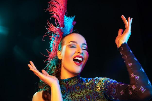 Schöne junge frau im karneval, stilvolles maskenkostüm mit federn an schwarzer wand im neonlicht