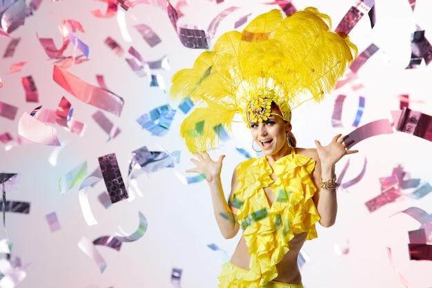 Schöne junge frau im karneval, stilvolles maskenkostüm mit federn, die auf weißem studiohintergrund mit leuchtendem neonkonfetti und bokeh tanzen. konzept der feier, festliche zeit, party