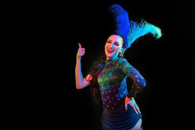 Schöne junge frau im karneval, stilvolles maskeradenkostüm mit federn auf schwarzem hintergrund im neonlicht.