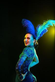 Schöne junge frau im karneval, stilvolles maskeradenkostüm mit federn auf schwarzer wand im neonlicht