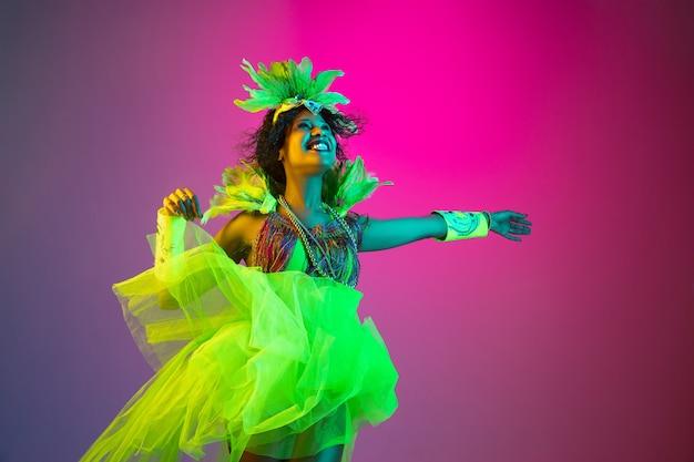 Schöne junge frau im karneval, stilvolles maskeradenkostüm mit federn, die auf gradientenhintergrund im neonlicht tanzen.