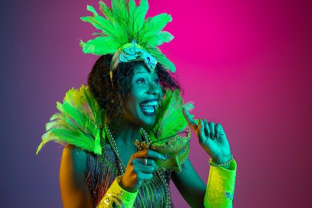 Schöne junge frau im karneval, stilvolles maskeradenkostüm mit federn, die auf gradientenhintergrund in neon tanzen.