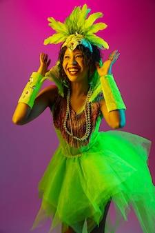 Schöne junge frau im karneval, stilvolles maskeradenkostüm mit federn, die auf gradientenwand in neon tanzen
