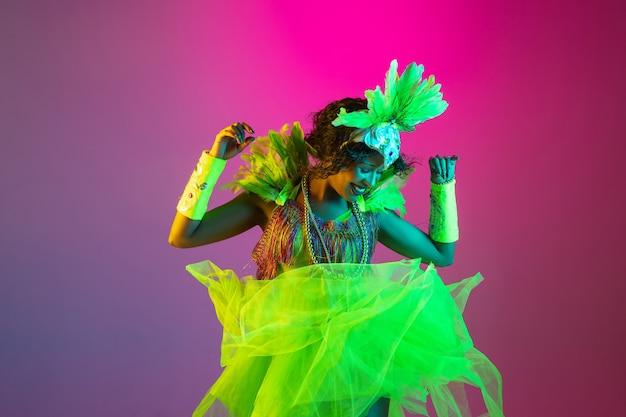 Schöne junge frau im karnevals- und maskeradenkostüm auf steigungsstudiohintergrund im neonlicht