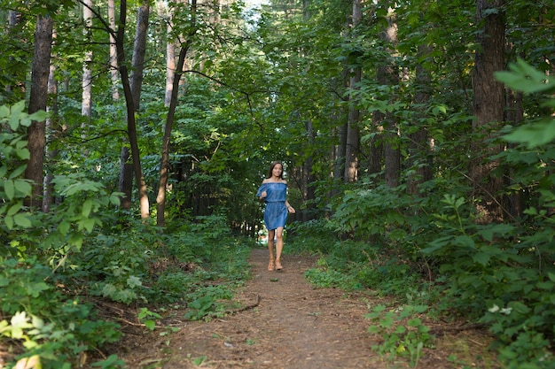 Schöne junge frau im kleid, das im sommerwald läuft