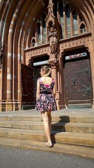 Schöne junge frau im kurzen kleid, die auf alten steintreppen an der kathotilc-kathedrale aufwirft