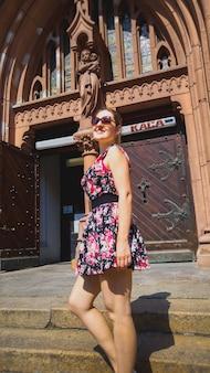Schöne junge frau im kurzen kleid, die auf alten steintreppen in der katholischen kathedrale in der europäischen stadt steht
