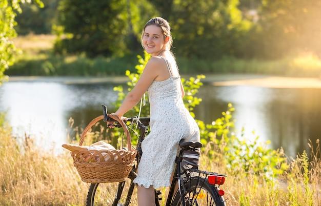 Schöne junge frau im kurzen kleid, die bei sonnenuntergang auf dem fahrrad am see fährt