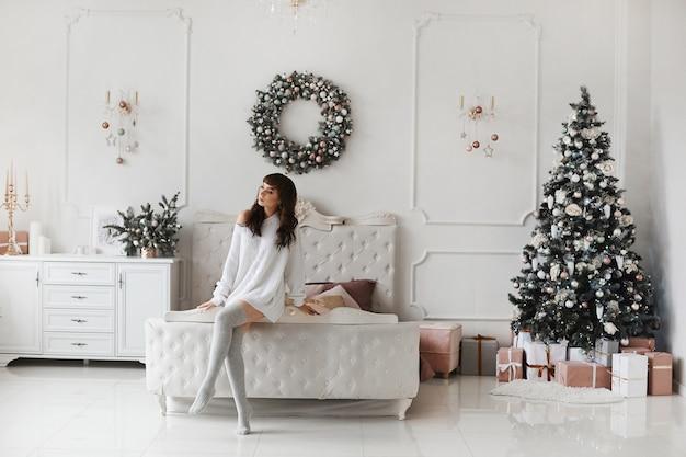 Schöne junge frau im kuscheligen pullover, der zu hause interieur für weihnachten dekoriert aufwirft.