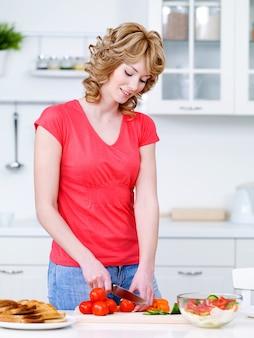 Schöne junge frau im lässigen schneiden von gemüse für salat in der küche