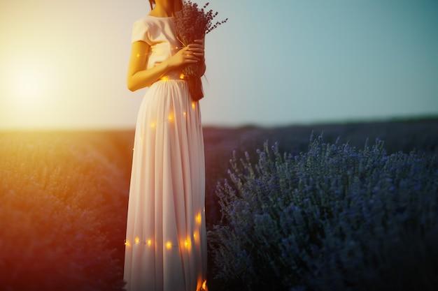 Schöne junge frau im langen blassen rosenkleid mit lichtern hält blumenstrauß von lavendel