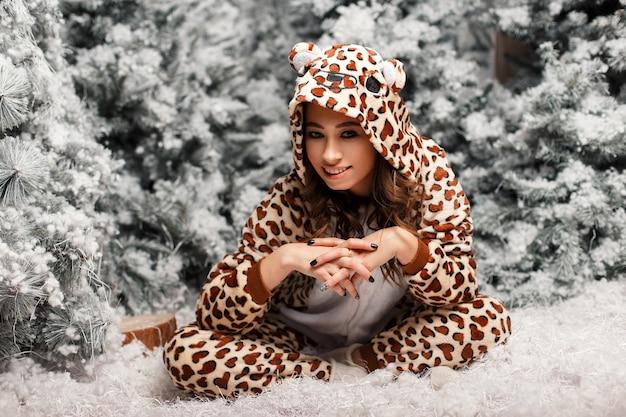 Schöne junge frau im lustigen pyjama, der nahe einem weihnachtsbaum mit schnee sitzt