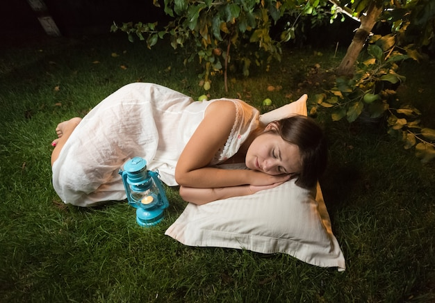 Schöne junge frau im nachthemd, die nachts auf gras im garten schläft