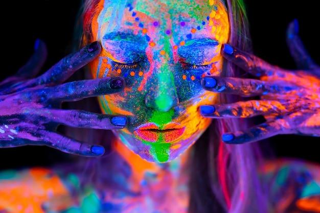 Schöne junge frau im neonlicht. porträt eines models mit fluoreszierendem make-up, das im uv-licht mit buntem make-up posiert