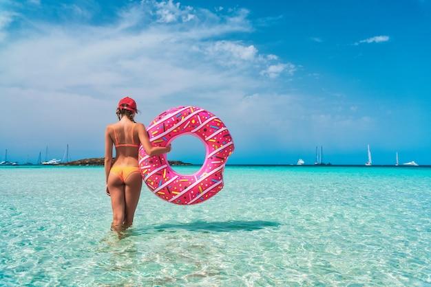 Schöne junge frau im orangefarbenen bikini mit rosa donutschwimmring im transparenten meer am sonnigen tag im sommer