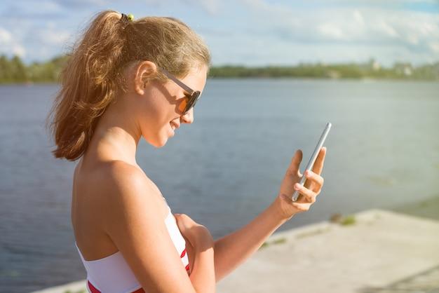 Schöne junge frau im park unter verwendung des mobiltelefons