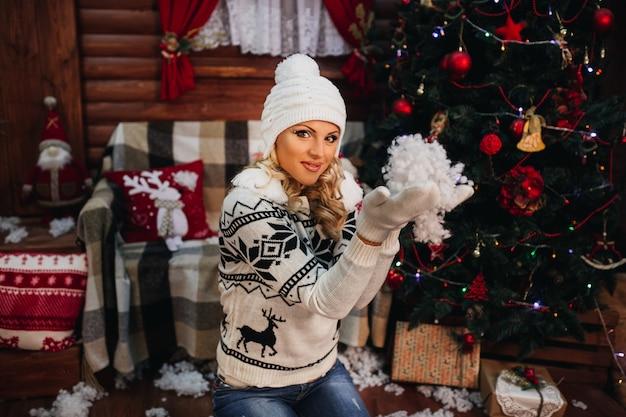 Schöne junge frau im pullover und im hut zu hause nahe dem weihnachtsbaum