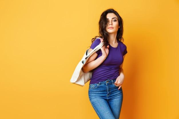 Schöne junge frau im purpurroten hemd, blue jeans, die mit tasche auf gelbem hintergrund aufwerfen